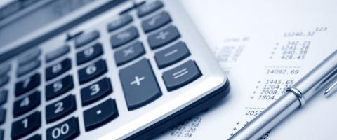 calculator, pen and budget figures
