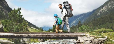 man hiking with young boy in mountains