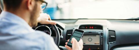 man using cell phone in car