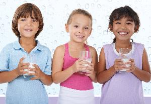 three school age kids with glasses of milk